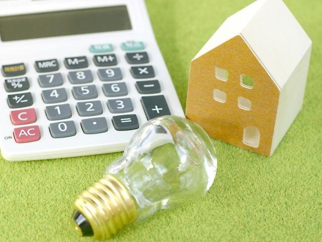 芝生に置かれた電卓と豆電球と家の模型